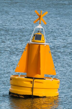 A yellow buoy is floating on the water surface in the Port of Rotterdam in the Netherlands.