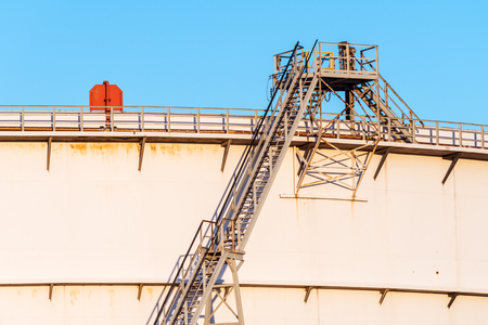 Detail of a staircase alongside a large oil storage tank on a sunny late afternoon in the harbour of Rotterdam. Stock Photo
