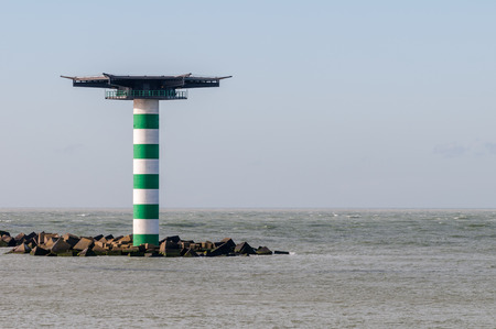 The green and white striped lighthouse Maasmond with heliplatform at the entrance of the Port of Rotterdam in the Netherlands. The lighthouse is situated at the end of pier Zuiderdam with concrete wave breakers.
