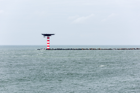 The red and white striped lighthouse with heliplatform at the entrance of the Port of Rotterdam in the Netherlands. The lighthouse is situated at the end of a pier with concrete wave breakers. Stock Photo