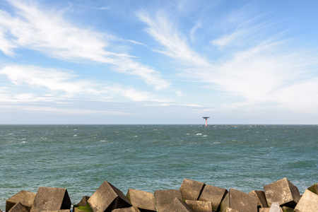 The lighthouse with heliplatform at the entrance of the Port of Rotterdam in the Netherlands. There are concrete wave breakers in the foreground and in the blue sky above are white cirrus clouds. Stock Photo