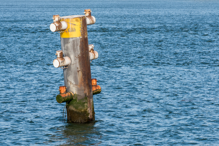 A rusty mooring pole in the harbor or Rotterdam isolated against  blue water.