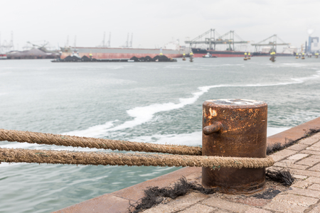 A iron bollard with a tied rope on a quay in the Port of Rotterdam in the Netherlands. In the background, slightly out of focus, is the industrial area of the Maasvlakte near Rotterdam.