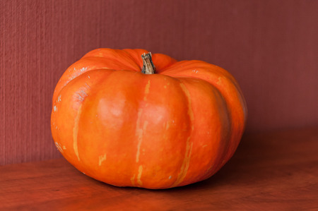 An orange pumkin is lying on a brown kitchen table, isolated on a red brown background.