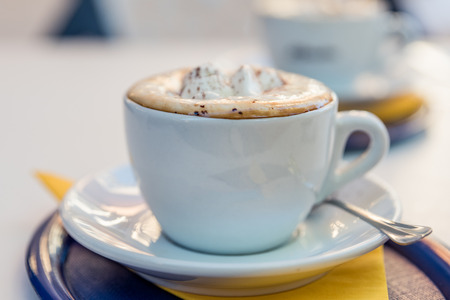 A cup of cappuccino coffee on a table with shallow depth of field. Stok Fotoğraf