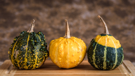Three pumpkins on a table with wooden cutting board and a rustic background.