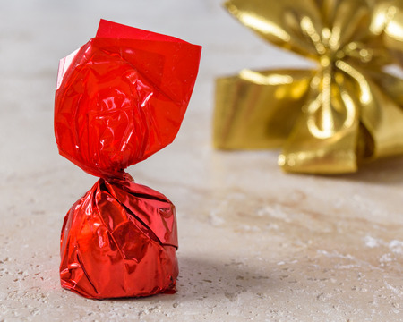 A cherry chocolate bonbon wrapped in red paper with a golden bow tie ribbon in the background. Stok Fotoğraf