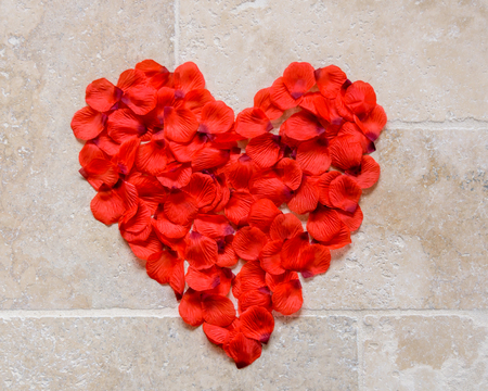 A heart symbol made of rose petals laid out on the floor as a concept of love and Valentines day.