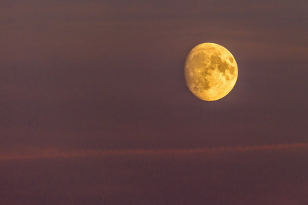 The moon is rising against a purple colored sky suring sunset. A little bit of cloud is visible. Stok Fotoğraf
