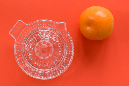 Glass manual juicer and a single orange isolated on a bright orange background. Stok Fotoğraf