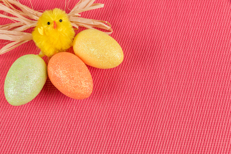 A cheerful easter chicken with three colored eggs on a pink background and space for text.