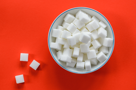 Top view of a white ceramic bowl filled with sugar cubes isolated on a red background. A few sugar cubes are spread on the table.