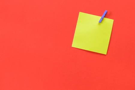 Yellow sticky note attached with a purple peg and copy space isolated on a red orange background. Stok Fotoğraf