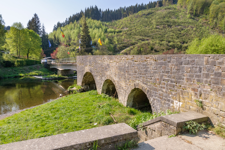 The historical bridge over the river Ourthe in the village Maboge near La Roche-en-Ardenne in Belgium. It is a sunny day during early spring. Stok Fotoğraf