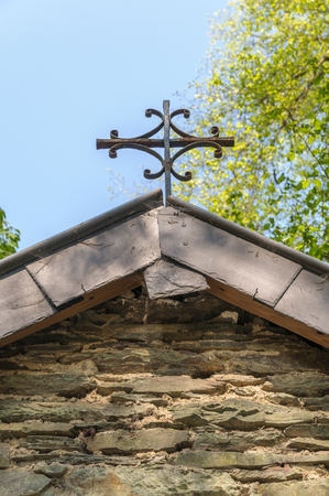 Close up of the rusty cross on the  rooftop of a little roadside chapel near Maboge in the Ardennes in Belgium. Stok Fotoğraf