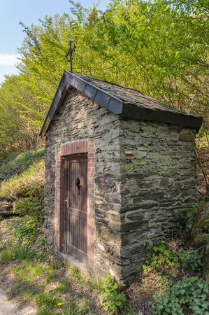 A little chapel near La Roche-en-Ardenne along the long distance hiking trail GR57 Sentiers de lOurthe, that leads through the Ardennes in Belgium. The sign of the route is on the wall of the chapel. Stok Fotoğraf