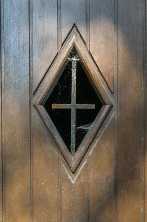 Close up of  a window in a wooden door of an old roadside chapel near La Roche-en-Ardenne in Belgium. In the window there is a rusty old iron cross with cobwebs. Stok Fotoğraf