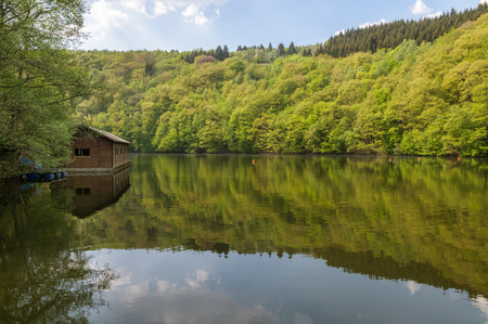 View of Lake Nisramont and the boathouse during spring with beautiful reflections and fresh green leaves on the trees. The lake is formed by a weir in the river Ourthe, the Barrage de Nisramont,  in the Ardennes, Belgium.