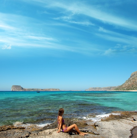 bautiful girl sitting on the coast and looking at blue sea water Stock Photo - 10594668