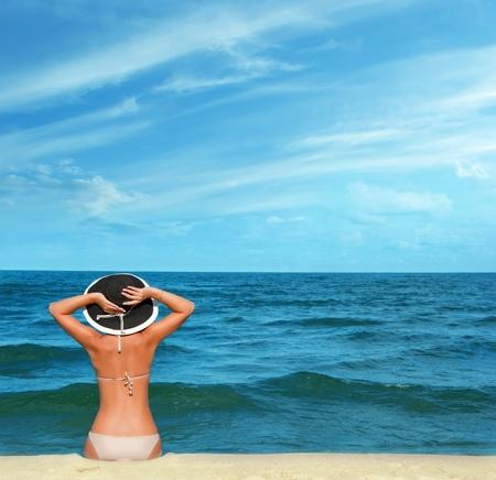 beautiful tanned girl watching the sea photo