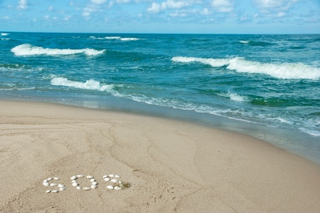 sos: sandy beach with a word SOS written with seashells Stock Photo