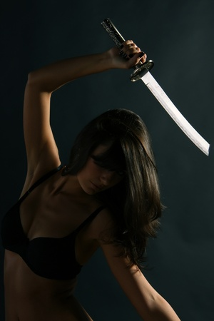 brunette with wakizashi sword in the darkness photo