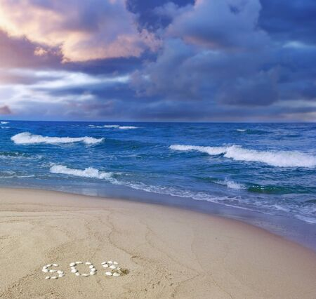 storm coming - sandy beach with a word SOS written with seashells and dark clouds over the waves photo