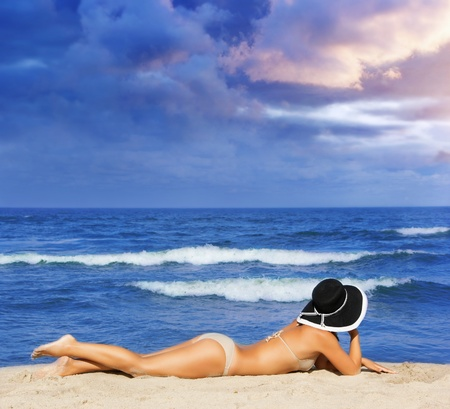 watching the coming storm - beautiful woman on the beach photo