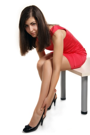 young woman having pain in feet after wearing high-heeled shoes photo