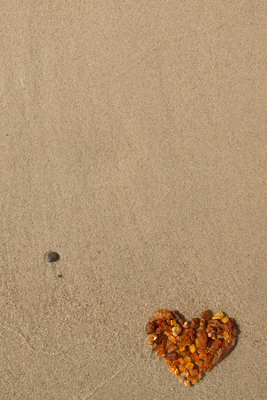 baltic sea: amber heart sand beach background with place for your text - baltic sea coast symbol