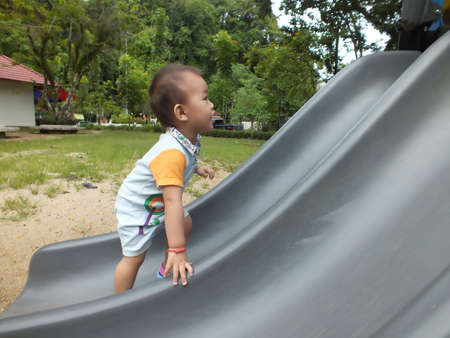 Cute baby playing on sliding board photo