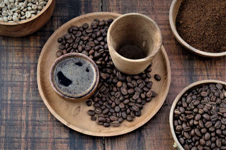Brewed black Robusta and Arabica coffee powder, roasted coffee beans and raw coffee beans. Stockfoto