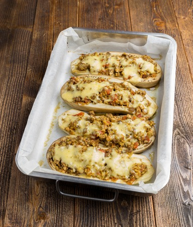 roasting pan: Baked zuchinni with chesse on a roasting pan on a wooden table.