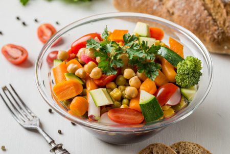 Vegetable salad in glass bowl with broccoli and tomatoes on white table.
