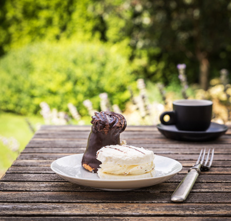 chocolaty: Sweet cakes on rustic desk with cup of coffee in the garden.