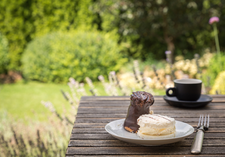 chocolaty: Sweet cakes on white plate with fork on rustic desk in the garden.