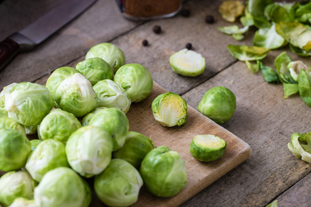 Raw brussels sprouts on wooden cutting desk on rustic table.