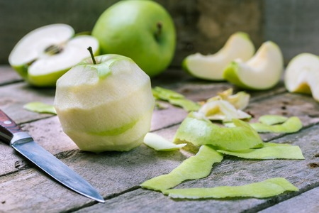 Green peeled apple on wooden desk with knife and apples behind.