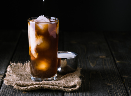 Iced coffee in a tall glass on jute background.