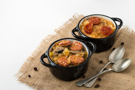 Slovak Christmas national cabbage soup in two small black pots with sausage on the jute background.