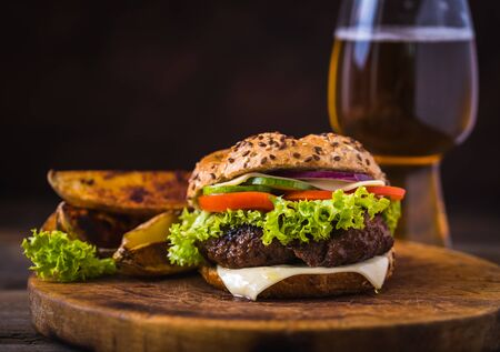 Home made hamburger with cheese and green salad and with american potatoes in behind. Wooden natural background.