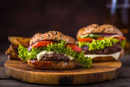 Home made hamburger with cheese and green salad. Wooden natural background. Stock Photo