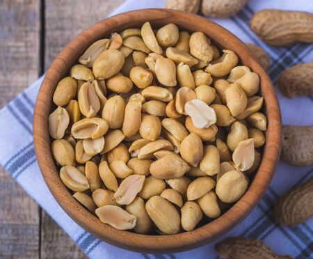 Peanuts in small wooden bowl on natural rustic desk.