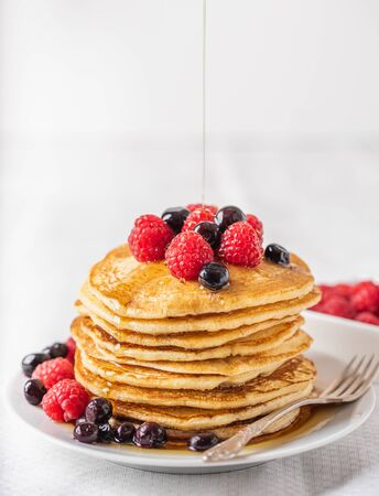 Sweet homemade pancakes with raspberries and blueberries on white plate.