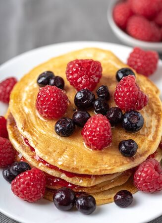 Sweet homemade pancakes with fruits on white plate.