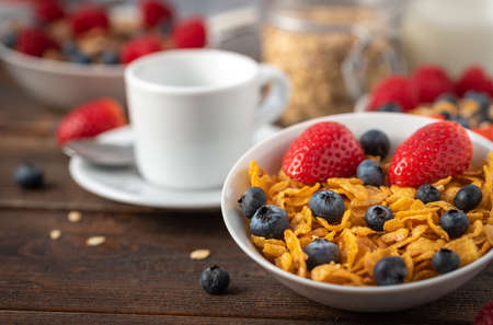 Corn flakes with blueberries and raspberries in white bowl in dark wooden desk.