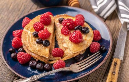 Sliced sweet homemade pancakes with raspberries and blueberries on blue plate on dark wooden desk. 免版税图像