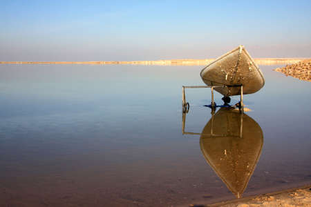 The old canoe reflecting in the mirror surface of the Dead Sea photo
