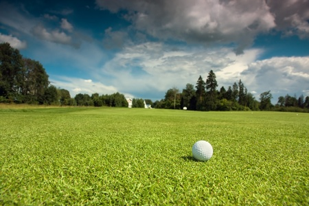 Golf ball on the course, green grass, blue sky and white clouds photo