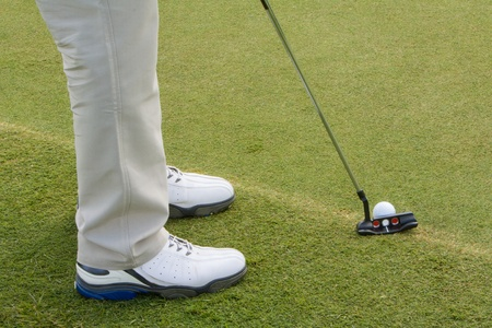 Closeup of legs with golf club and ball on tee grass, golfer prepares to putt photo